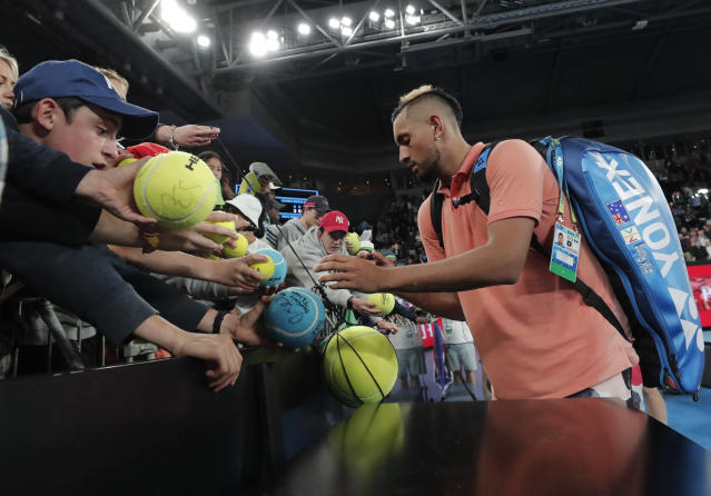 Australia's Nick Kyrgios signs autographs after defeating France's Gilles Simon in their second round singles match at the Australian Open tennis championship in Melbourne, Australia, Thursday, Jan. 23, 2020. (AP Photo/Lee Jin-man)