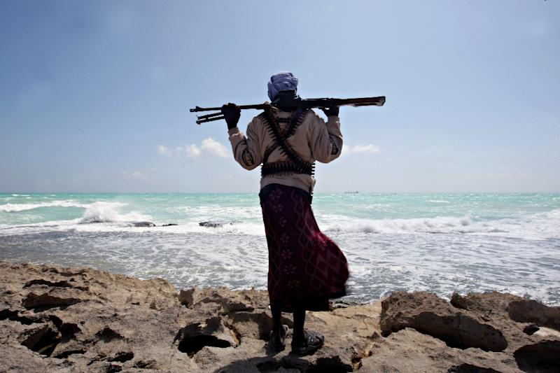 An armed Somali pirate walks along the coastline near Hobyo in 2010