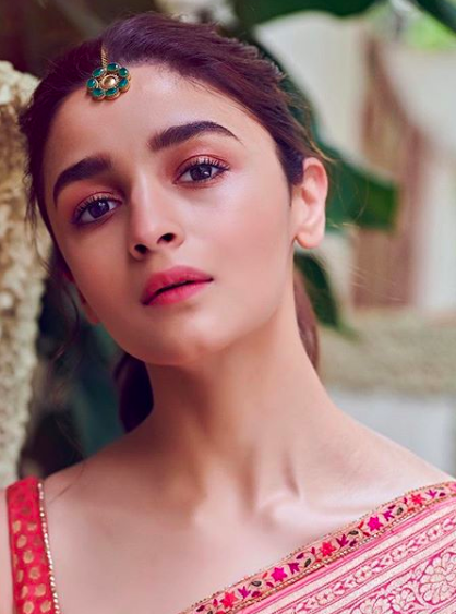 """""""A dewy intensity, superbly-soft look from the versatile Alia Bhatt. A gentle vision of beauty with petal textured skin and creamy, crease-free eyes and lips, but the expression in her eyes tells a different tale of steely strength and conviction. <strong>Get this look </strong>with fully prepped skin and minimal use of foundation and liquid highlighter for the dewiness. Using your fingers, blend MyGlamm's <a href=""""https://fave.co/2Je3oon"""" rel=""""nofollow noopener"""" target=""""_blank"""" data-ylk=""""slk:Butterlicious Liquid Matte Lipstick in Rosé"""" class=""""link rapid-noclick-resp"""">Butterlicious Liquid Matte Lipstick in Rosé</a> onto the eyelids and set it with a hint of translucent powder. Define and fill the eyebrows with a brown brow powder and mascara. Use the same shade of Butterlicious on the lips and Voila!"""""""