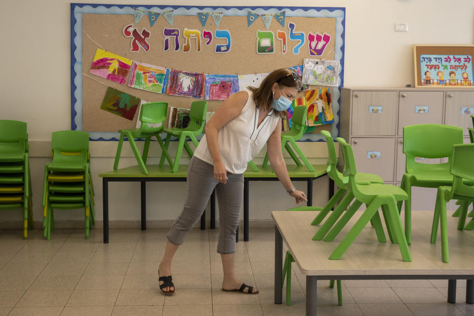 Ravit Shamay, a principal of a kindergarten and junior division of a school, sets up a classroom, in Tirat Carmel, Israel, Thursday, Oct. 29, 2020. Israeli children are scheduled to return to classrooms Nov. 1 after a six-week closure of schools during a nationwide lockdown. (AP Photo/Ariel Schalit)