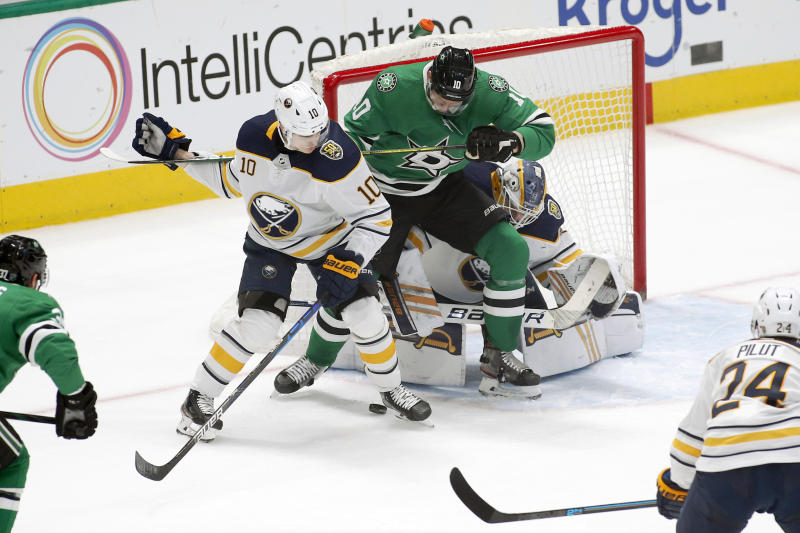 Buffalo Sabres defenseman Henri Jokiharju, left, and Dallas Stars right wing Corey Perry, right, battle for the puck in the crease during the first period of an NHL hockey game in Dallas, Thursday, Jan. 16, 2020. (AP Photo/Ray Carlin)