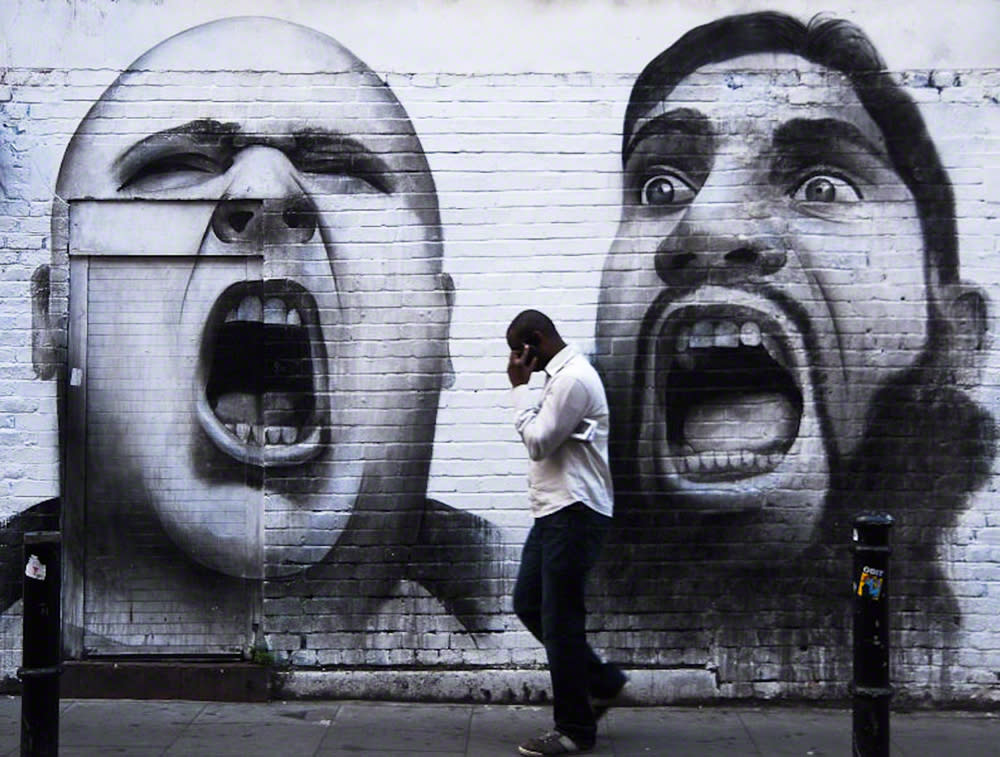 A man ignores a powerful mural in Shoreditch, London. The photograph, taken by Anka Sliwa, from the UK, was the winner for 'First Shot - Big City' (Travel Photographer of the Year)