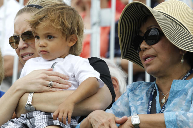 Kultida Woods, Tiger Wood's mother, right, stands beside Tiger's son Charlie, center, as Woods approaches the ninth green during the second round of the Honda Classic golf tournament in Palm Beach Gardens, Fla., Friday, March 2, 2012. The woman at left is unidentified.(AP Photo/Lynne Sladky)