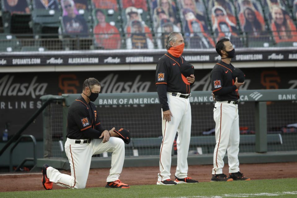 San Francisco Giants manager Gabe Kapler, left, kneels during the national anthem prior to the team's baseball game against the Texas Rangers on Saturday, Aug. 1, 2020, in San Francisco. (AP Photo/Ben Margot)