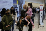 Members of the Mogul family are reunited as the grandfather carries his grandchildren, who arrived with their mother, third left, on a flight from Charlotte, North Carolina, in the U.S., at Terminal 5 of Heathrow Airport in London, Monday, Aug. 2, 2021. Travelers fully vaccinated against coronavirus from the United States and much of Europe were able to enter Britain without quarantining starting today, a move welcomed by Britain's ailing travel industry. (AP Photo/Matt Dunham)