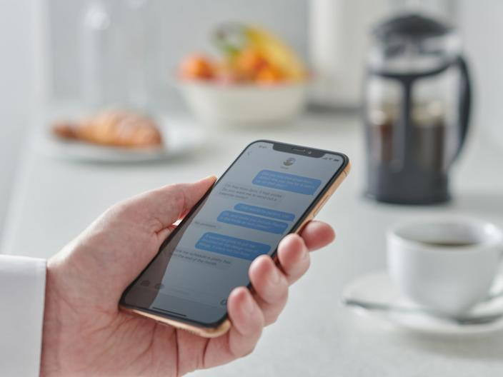 person looking at phone kitchen counter