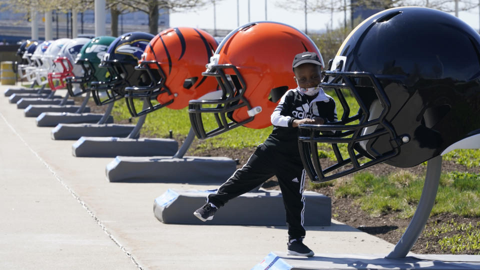 Joseph Toliver, 4, plays on one of the 32 NFL team helmets on display, Tuesday, April 13, 2021, in downtown Cleveland. Forced to cancel last year's NFL Draft in Las Vegas, the league is using lessons learned while plowing through an unprecedented, socially-distanced 2020 season and holding the Super Bow in Tampa, to have a draft that will look much more like normal — well, the new normal — with fans wearing their favorite team's colors and required masks.(AP Photo/Tony Dejak)