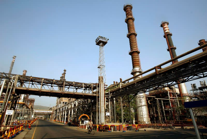 FILE PHOTO: A worker rides a bicycle at the Bharat Petroleum Corporation refinery in Mumbai