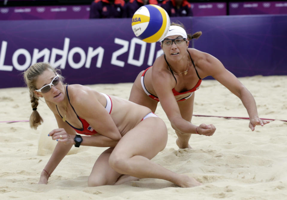 The United States's Misty May Treanor, right, dives over her teammate Kerri Walsh Jennings during a women's semi-final beach volleyball match against China at the 2012 Summer Olympics, Tuesday, Aug. 7, 2012, in London. (AP Photo/Dave Martin)