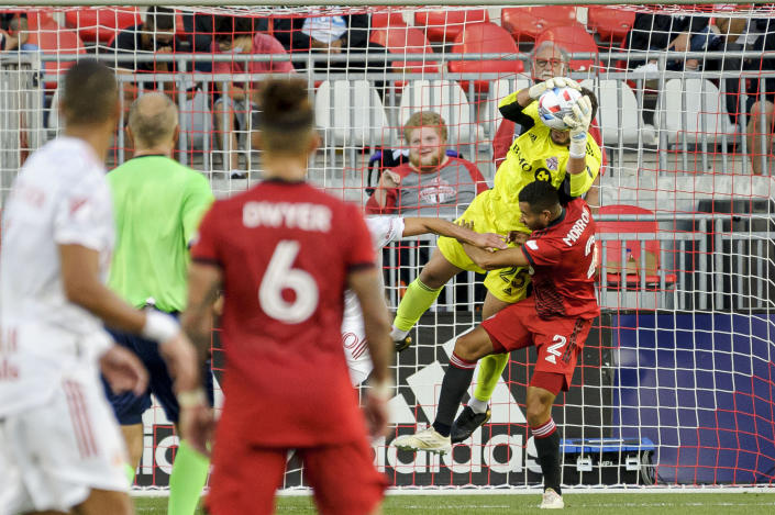 Toronto FC goalkeeper Alex Bono (25) and defender Justin Morrow (2) collide during the first half of the team's MLS soccer match against the New York Red Bulls on Wednesday, July 21, 2021, in Toronto. (Chris Katsarov/The Canadian Press via AP)