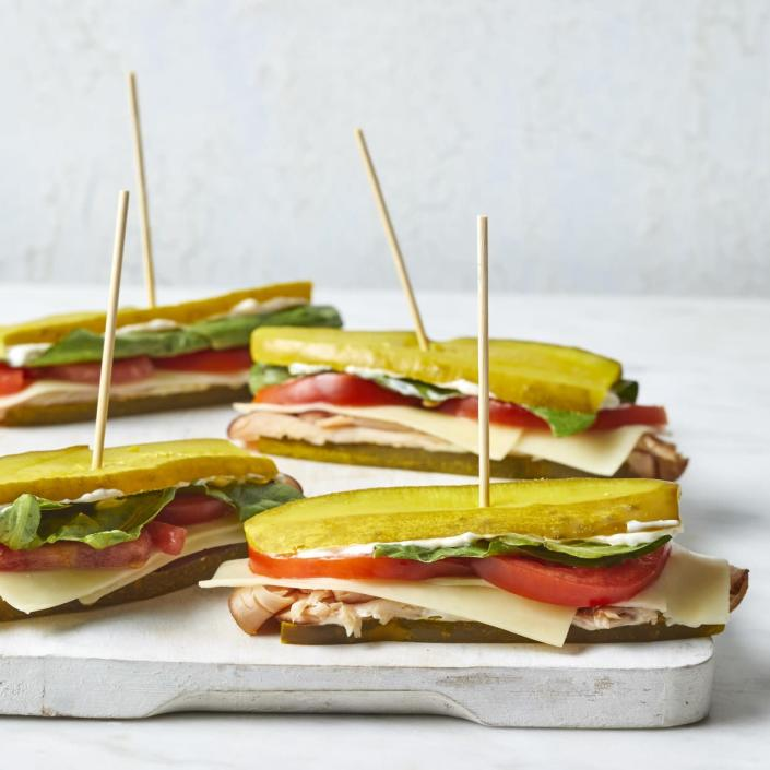 """<p>Cut down on carbs by swapping out the bread for slices of pickle to make these fun turkey and Cheddar sandwiches. Roma tomatoes are the perfect oblong shape for these mini sandwiches but feel free to use regular tomatoes--simply cut the slices in half so they fit nicely on the pickle sandwich. These sandwiches are an easy lunch, but they're also great on a party tray for a casual get-together. <a href=""""https://www.eatingwell.com/recipe/276621/pickle-sub-sandwiches-with-turkey-cheddar/"""" rel=""""nofollow noopener"""" target=""""_blank"""" data-ylk=""""slk:View Recipe"""" class=""""link rapid-noclick-resp"""">View Recipe</a></p>"""