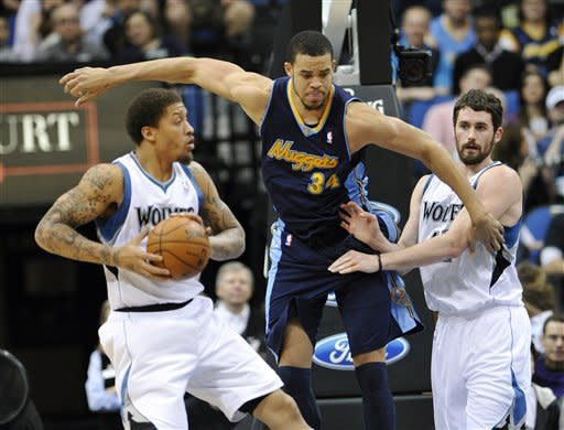 Denver Nuggets' Javale McGee (34) tries to make his way past Minnesota Timberwolves' Kevin Love , right, as Michael Beasley hangs onto the ball in the first half of an NBA basketball game Sunday, March 25, 2012, in Minneapolis. (AP Photo/ Jim Mone)