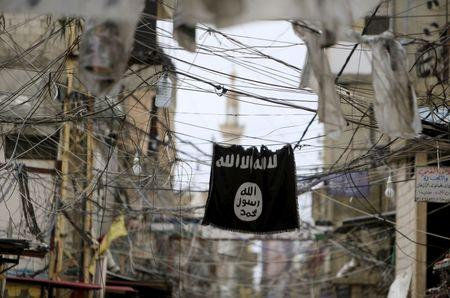 An Islamic State flag hangs amid electric wires over a street in Ain al-Hilweh Palestinian refugee camp, near the port-city of Sidon, southern Lebanon