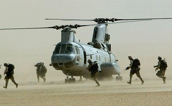 U.S. marines from the 15th Marine Expeditionary Unit run in a line to a CH-46 Sea Knighthelicopter during a drill in the Kuwaiti desert near Iraq in thisFebruary 23, 2003 (Reuters)