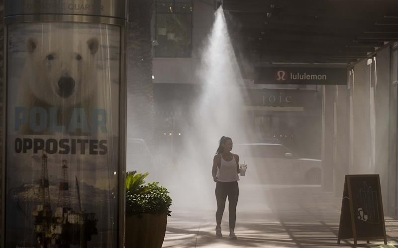Michelle de la Vara gets a break from the heat while walking in Scottsdale, Ariz., on Tuesday. The National Weather Service says Phoenix broke its heat record for Aug. 20 on Tuesday afternoon, reaching a high of 113 degrees.
