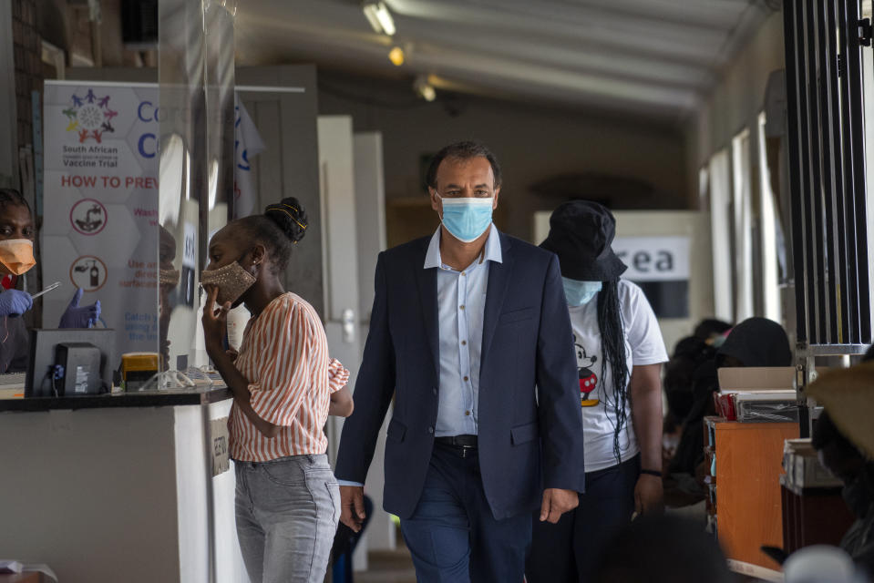 FILE- In this Nov. 30, 2020 file photo, Shabir Madhi, Professor of Vaccinology at the University of Witwatersrand, walks through a COVID-19 vaccine trial facility set at Soweto's Chris Sani Baragwanath Hospital outside Johannesburg. South Africa is scrambling to come up with a new vaccination strategy to combat COVID-19 following its suspension of the rollout of the AstraZeneca vaccine, after a preliminary test showed weak results in protecting the variant dominant in this country. Among the possibilities being considered are giving one dose of AstraZeneca in the hopes it will protect against severe disease and death from the variant. (AP Photo/Jerome Delay, File)