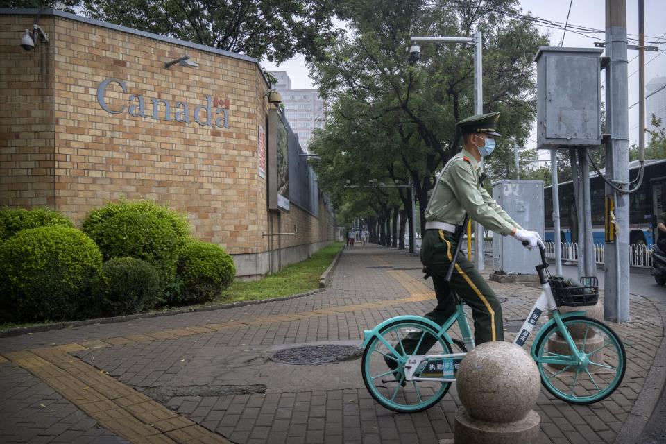 A Chinese paramilitary policeman rides a bicycle past the Canadian Embassy in Beijing, Saturday, Sept. 25, 2021. Two Canadians detained in China on spying charges were released from prison and flown out of the country on Friday, Prime Minister Justin Trudeau announced Friday, hours after a top executive of Chinese communications giant Huawei Technologies resolved criminal charges against her in a deal with the U.S. Justice Department. (AP Photo/Mark Schiefelbein)