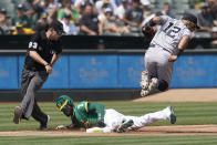 Oakland Athletics' Starling Marte, bottom, steals third base under New York Yankees third baseman Rougned Odor (12) as umpire Will Little (93) watches during the third inning of a baseball game in Oakland, Calif., Saturday, Aug. 28, 2021. (AP Photo/Jeff Chiu)