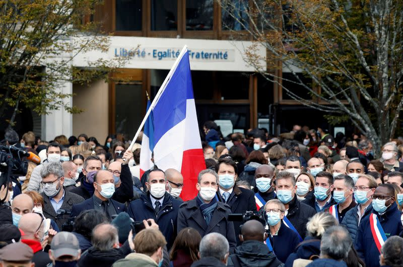 FILE PHOTO: People gather in front of the Bois d'Aulne college after the attack in the Paris suburb of Conflans St Honorine