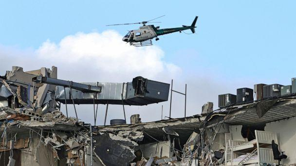 PHOTO: A Miami-Dade Police helicopter flies over the Champlain Towers South Condo after the multistory building partially collapsed, June 24, 2021, in Surfside, Fla. (David Santiago/Miami Herald via AP)