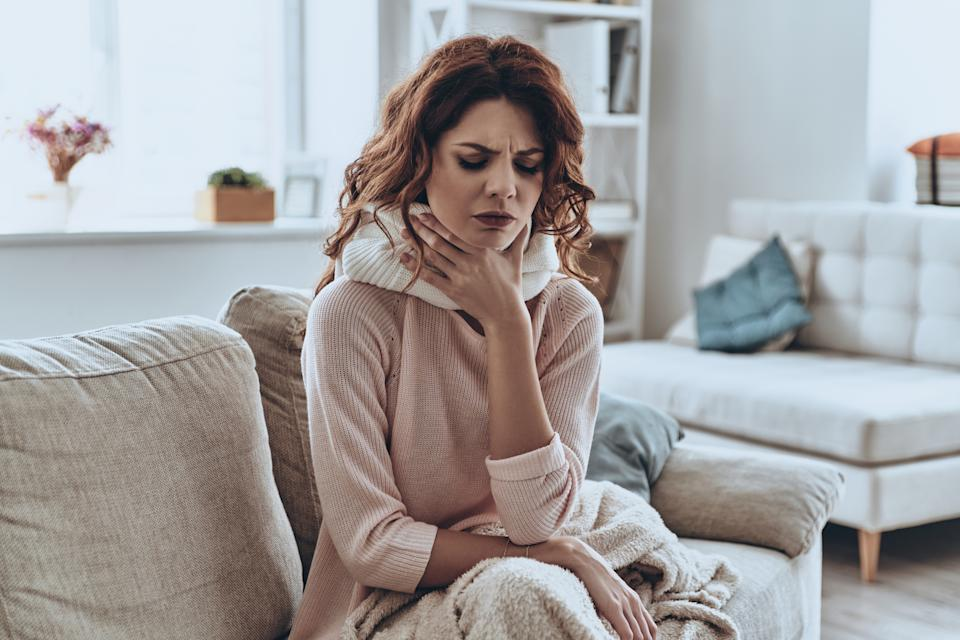 Sick young women covered with blanket coughing while sitting on the sofa at home