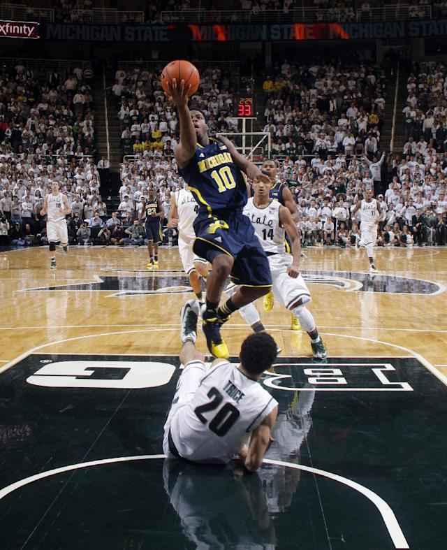 Michigan's Derrick Walton Jr. (10) goes over Michigan State's Travis Trice (20) for a layup during the second half of an NCAA college basketball game, Saturday, Jan. 25, 2014, in East Lansing, Mich. Walton had 19 points in Michigan's 80-75 win. (AP Photo/Al Goldis)