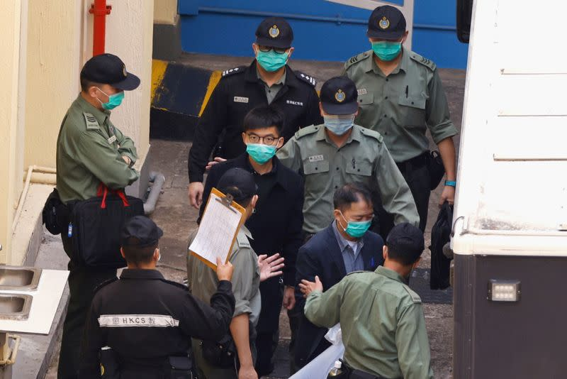 Pro-democracy activists Joshua Wong and Wu Chi-wai walk to a prison van to head to court, over national security law charges, in Hong Kong