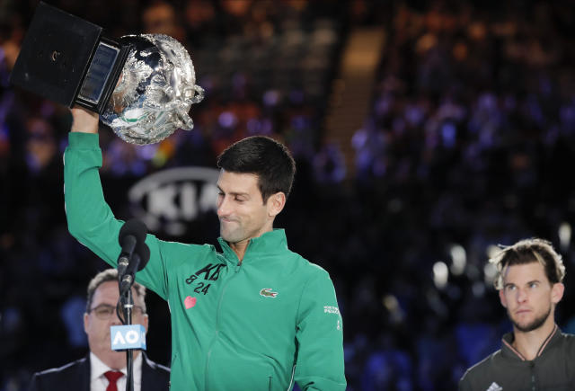 Serbia's Novak Djokovic, left, holds the Norman Brooks Challenge Cup after defeating Austria's Dominic Thiem in the final of the Australian Open tennis championship in Melbourne, Australia, Monday, Feb. 3, 2020. (AP Photo/Lee Jin-man)
