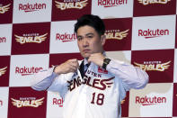 FILE - Former New York Yankees pitcher Masahiro Tanaka puts on his new Rakuten Golden Eagles uniform for a photo session during a news conference in Tokyo, in this Saturday, Jan. 30, 2021, file photo. Host Japan is favored to win at the Tokyo Games. (AP Photo/Eugene Hoshiko, File)