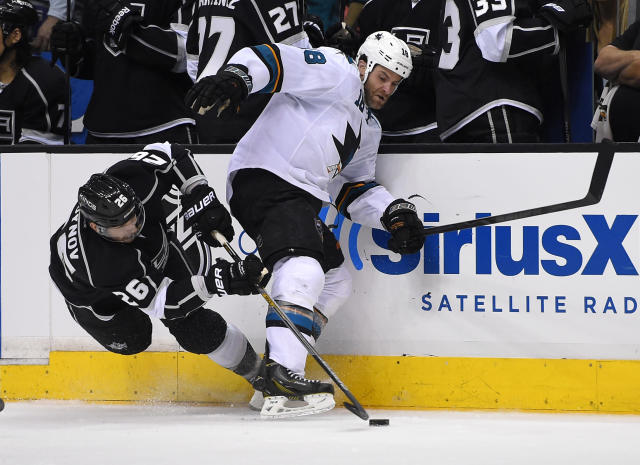 Los Angeles Kings defenseman Slava Voynov, of Russia, left, tangle with San Jose Sharks right wing Mike Brown as he passes the puck during the third period in Game 3 of an NHL hockey first-round playoff series, Tuesday, April 22, 2014, in Los Angeles. (AP Photo/Mark J. Terrill)