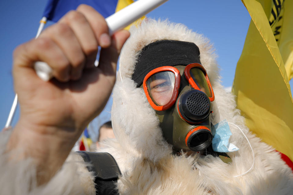 An anti-vaccination protester wears a gas mask during a rally outside the parliament building in Bucharest, Romania, Sunday, March 7, 2021. Some thousands of anti-vaccination protestors from across Romania converged outside the parliament building protesting against government pandemic control measures as authorities announced new restrictions amid a rise of COVID-19 infections. (AP Photo/Vadim Ghirda)