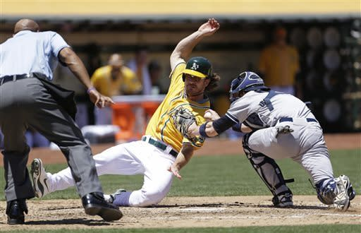 Oakland Athletics' John Jaso, center, slides into home plate to score the A's second run as New York Yankees catcher Chris Stewart, right, makes a late tag and home plate umpire CB Bucknor, left, looks on during the third inning of a baseball game on Thursday, June 13, 2013, in Oakland, Calif. (AP Photo/Eric Risberg)