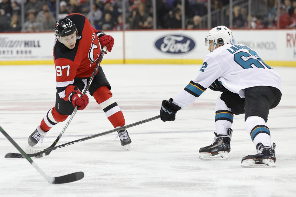 San Jose Sharks right wing Kevin Labanc (62) blocks a shot by New Jersey Devils left wing Nikita Gusev (97) during the second period of an NHL hockey game, Thursday, Feb. 20, 2020, in Newark, N.J. (AP Photo/Kathy Willens)
