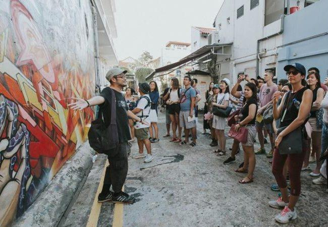 Visitors take in graffiti in the Kampong Glam neighborhood. Photo: D'Tour of Kampong Glam / Aliwal Arts Centre