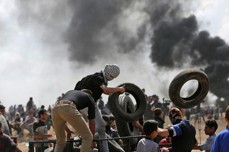 Palestinians carry tires to be burned during clashes with Israeli forces near the border between the Gaza Strip and Israel