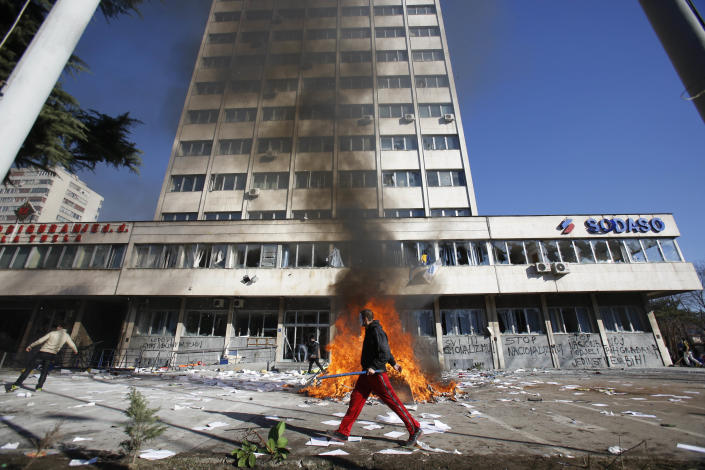 FILE - In this Friday, Feb. 7, 2014 file photo, a Bosnian protester walks past a local government building during protests in Tuzla, Bosnia. The violence engulfing Bosnia in recent days, with scenes of burning government buildings and protesters pelting police with stones, has many root causes. One of them is the failed privatizations of state-owned companies. (AP Photo/Amel Emric, File)