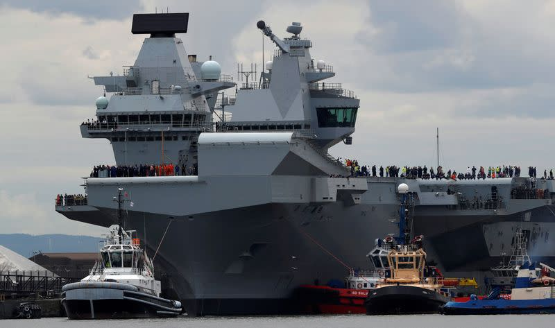 FILE PHOTO: The British aircraft carrier HMS Queen Elizabeth is pulled from its berth by tugs before its maiden voyage, in Rosyth, Scotland