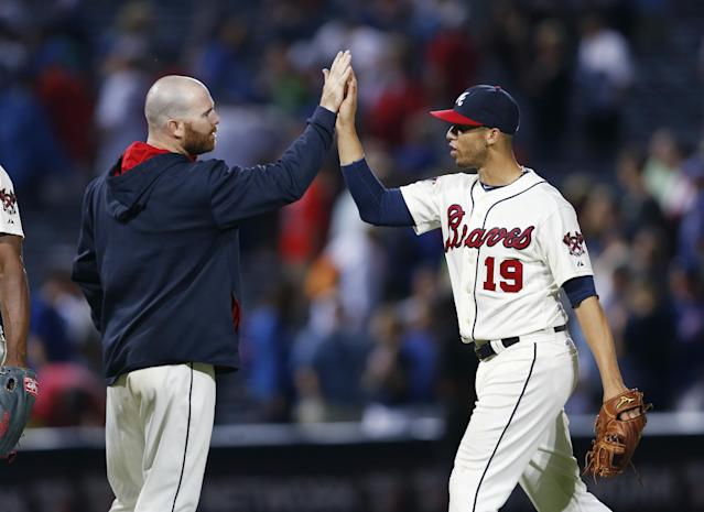 Atlanta Braves catcher Ryan Doumit (4) and shortstop Andrelton Simmons (19) celebrate the Braves' 2-0 victory over the Chicago Cubs in a baseball game Saturday, May 10, 2014, in Atlanta. Doumit drove in the game-winning run with a pinch-hit double in the seventh inning. (AP Photo/John Bazemore)
