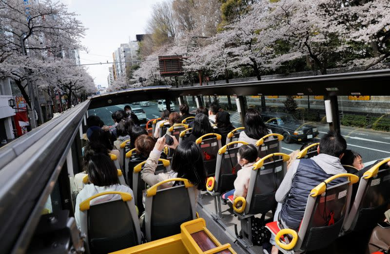 Passengers wearing protective face masks enjoy viewing blooming cherry blossoms from an open-top sightseeing bus, operated by Hato Bus Co., after Japan's government lifted the coronavirus disease (COVID-19) state of emergency in the Tokyo