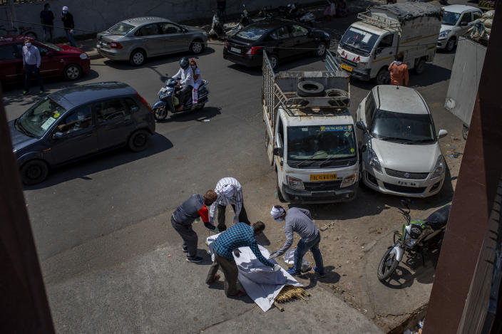 Members of the family of a COVID-19 victim put a shroud over the body lying on a road outside a crematorium in New Delhi, India, Saturday, April 24, 2021. Delhi has been cremating so many bodies of coronavirus victims that authorities are getting requests to start cutting down trees in city parks, as a second record surge has brought India's tattered healthcare system to its knees. (AP Photo/Altaf Qadri)