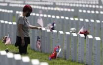 Cleveland resident Rosemay Thomas touches the tombstone of her husband at the Ohio Western Reserve National Cemetery on Memorial Day in Seville