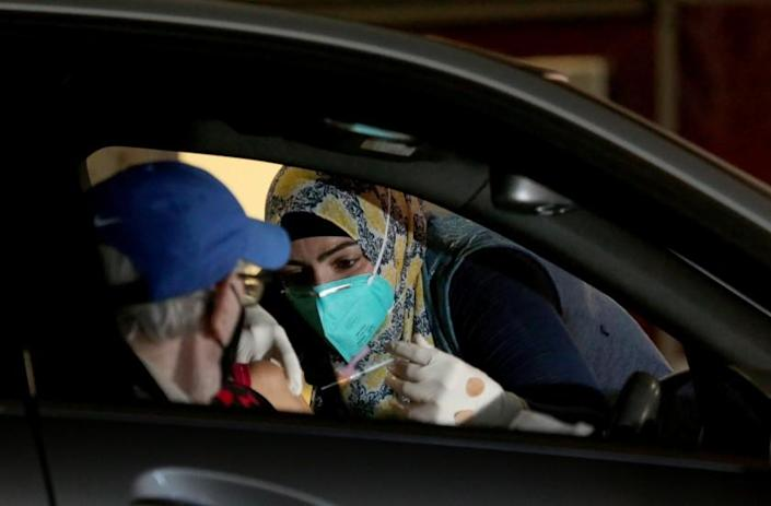 LONG BEACH, CA. - JAN. 21, 2021. Dr. Sarah Mohtadi administers coronavirus vaccine at a drive-in vaccination site at the Long Beach Convention Center on Thursday, Jan. 21, 2021. (Luis Sinco/Los Angeles Times)