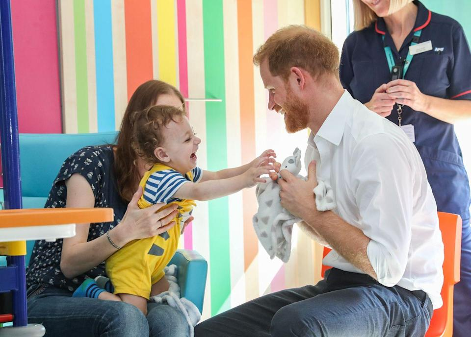 <p>Prince Harry plays with a young child during a visit to Sheffield Children's Hospital.</p>