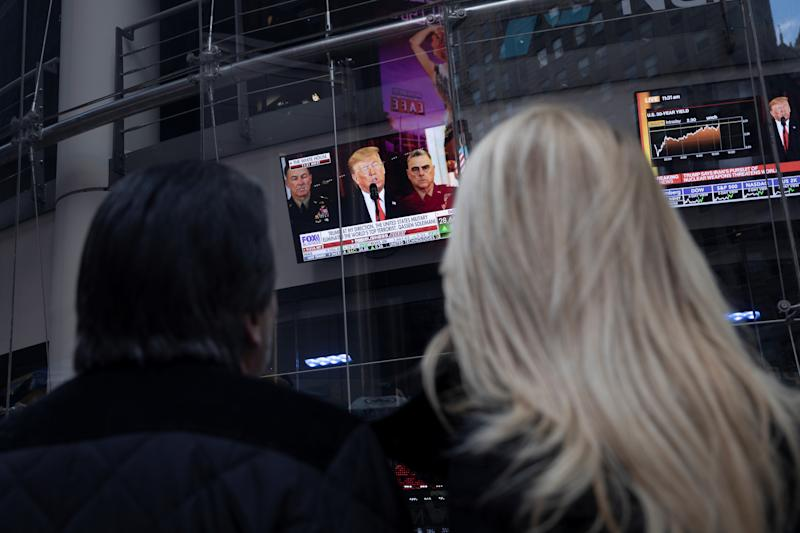 People watch as U.S. President Donald Trump is seen on screens delivering a statement from the White Housein New York