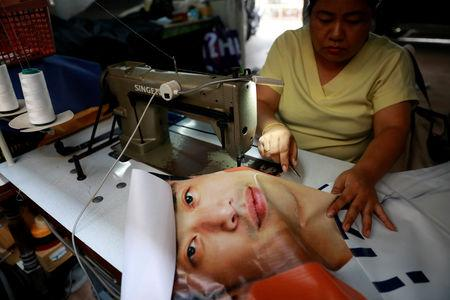 A woman sews a tote bag out of old election campaign posters in Bangkok, Thailand April 8, 2019. REUTERS/Soe Zeya Tun