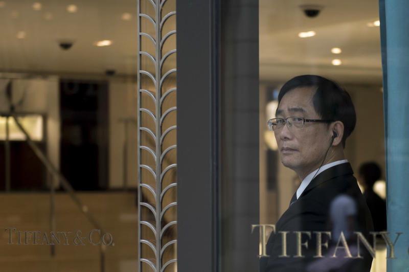 A security guard is seen standing by the entrance of a luxury jewellery store in Hong Kong, on August 7, 2014 (AFP Photo/Alex Ogle)