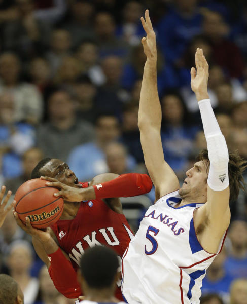 Western Kentucky guard T.J. Price, left, is fouled by Kansas center Jeff Withey (5) during the first half of a second-round game in the NCAA college basketball tournament at the Sprint Center in Kansas City, Mo., Friday, March 22, 2013. (AP Photo/Orlin Wagner)