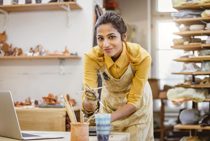 Young Woman Creating Pottery, Using Laptop