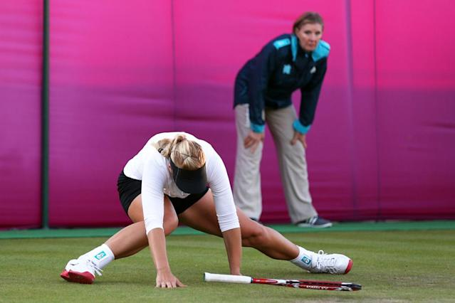 Sabine Lisicki of Germany slips on the grass and falls to the floor during the Women's Singles Tennis match against Ons Jabeur of Tunisia on Day 2 of the London 2012 Olympic Games at the All England Lawn Tennis and Croquet Club in Wimbledon on July 29, 2012 in London, England. (Photo by Clive Brunskill/Getty Images)