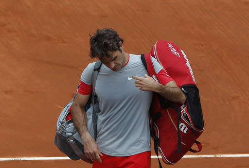 Switzerland's Roger Federer leaves the court after losing to Latvia's Ernests Gulbis during their fourth round match of the French Open tennis tournament at the Roland Garros stadium, in Paris, France, Sunday, June 1, 2014. Gulbis won 6-7, 7-6, 6-2, 4-6, 6-3. (AP Photo/Michel Euler)